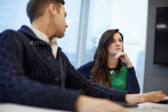 A man and woman seated at a meeting in an office. - Stock Photo - Images