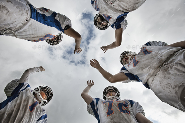 A group of football players, young people in sports uniform and protective helmets, in a team huddle viewed from below.