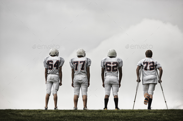 A group of football players, young people in sports uniform and protective helmets. One person using crutches.