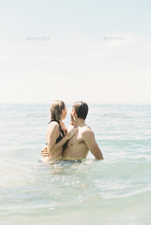 Couple hugging each other, in waist deep water. - Stock Photo - Images