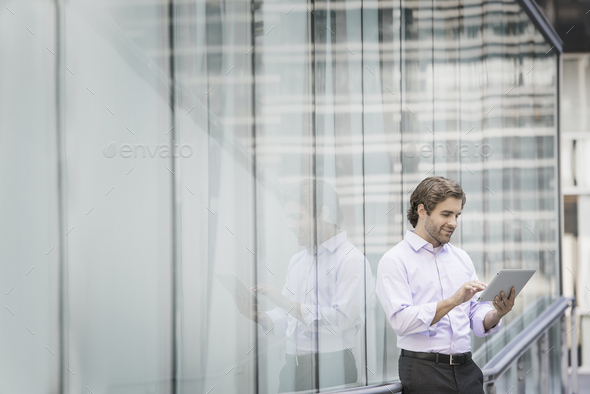 A man standing outside a building with large glass exterior panels, using a digital tablet. - Stock Photo - Images