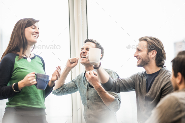 Four work colleagues on a break, laughing and raising their coffee cups. - Stock Photo - Images