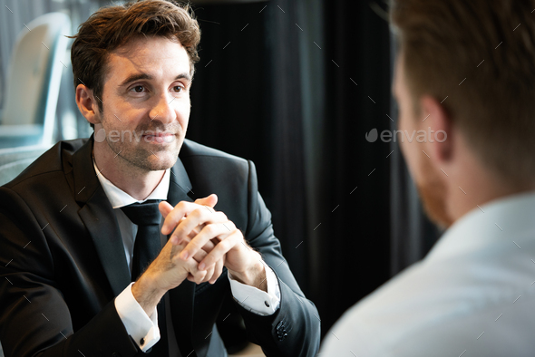 Successful businessman smiling while discussing with partner during meeting at coffee break - Stock Photo - Images