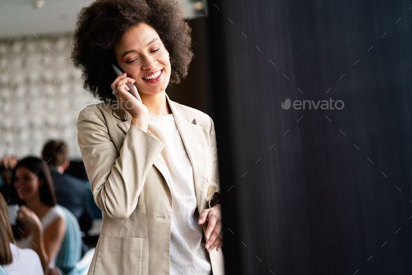 Beautiful african corporate worker talking on mobile phone - Stock Photo - Images