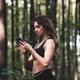 Girl in sports uniform using heahones and looking at phone. Physical activities in nature - PhotoDune Item for Sale