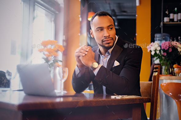 Thoughtful male in a cafe using laptop. - Stock Photo - Images