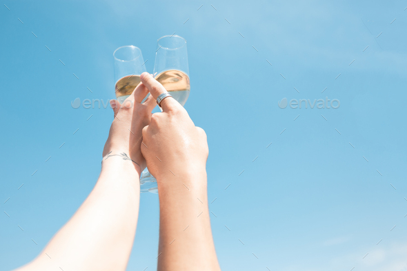 Seasonal feast at beach resort. Close up hands of friends celebrating, resting, having fun, clinking - Stock Photo - Images