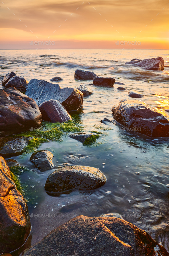 Seascape with rocks in water at sunset. - Stock Photo - Images