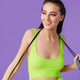 Photo of sporty joyful woman holding jump rope and smiling - PhotoDune Item for Sale