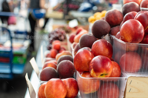 Picture of sweet, tasty and fresh peaches lying in small plastic boxes in the store - Stock Photo - Images