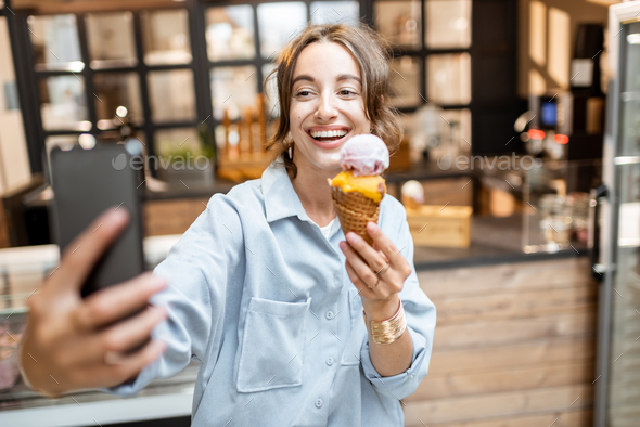 Cheerful woman with ice cream in the shop - Stock Photo - Images