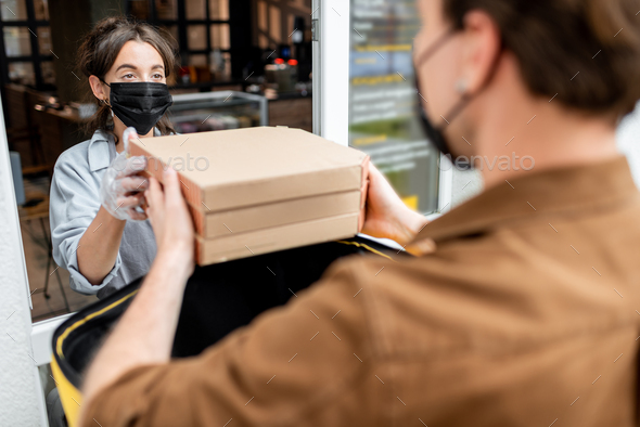 Courier taking an order for delivering from the shop window - Stock Photo - Images