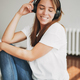 Portrait of smiling young woman in white t-shirt and jeans listening music by headphones - PhotoDune Item for Sale
