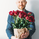 Attractive adult bearded man holding beautiful bouquet of dark peonies in craft paper - PhotoDune Item for Sale