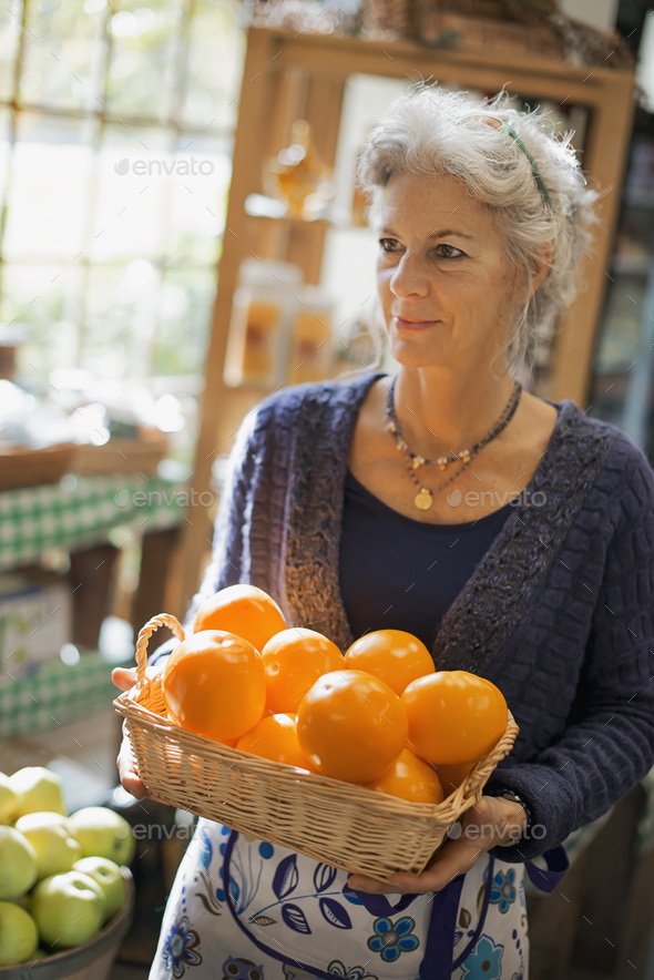 Organic Farmer at Work. A woman carrying a box of large oranges. - Stock Photo - Images