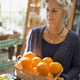 Organic Farmer at Work. A woman carrying a box of large oranges. - PhotoDune Item for Sale