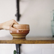 Farm to Table. A person reaching up for a pottery bowl in a domestic kitchen. - PhotoDune Item for Sale
