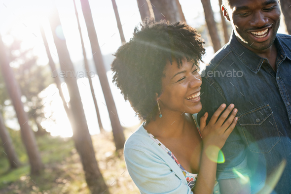 A happy couple in a shady spot in woodland in summer. Hugging and holding each other. - Stock Photo - Images