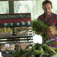 A farm stand with fresh organic vegetables and fruit.  A man holding bunches of carrots. - PhotoDune Item for Sale