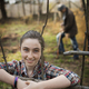 A young girl leaning on a fence, on an organic farm. A man digging the soil in the background. - PhotoDune Item for Sale