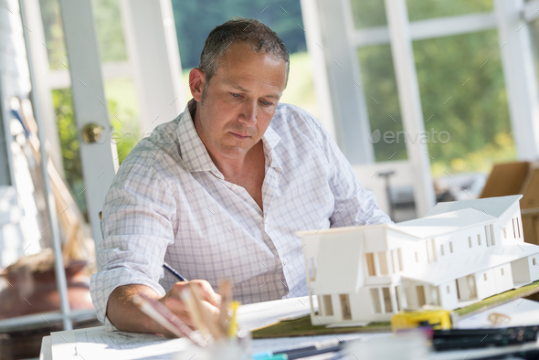 A man using a pencil drawing on an architect's plan, redesigning and renovation - Stock Photo - Images
