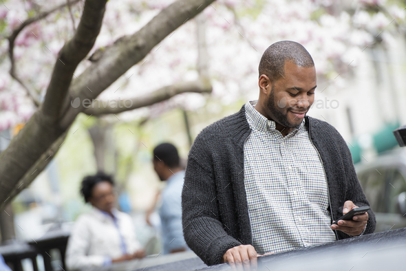 Spring in the city,A young man checking his phone and texting. A couple in the background - Stock Photo - Images