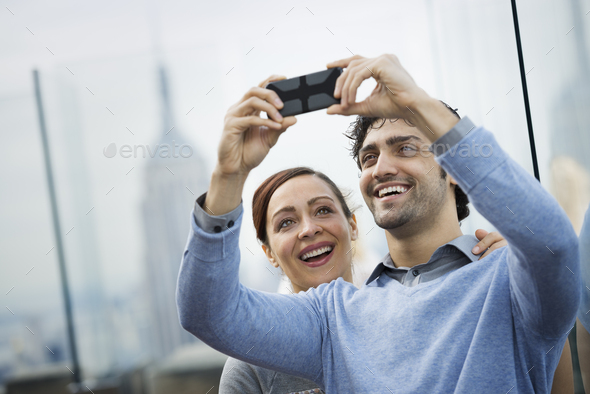 A young couple taking photographs with a mobile phone at a viewpoint over a city - Stock Photo - Images