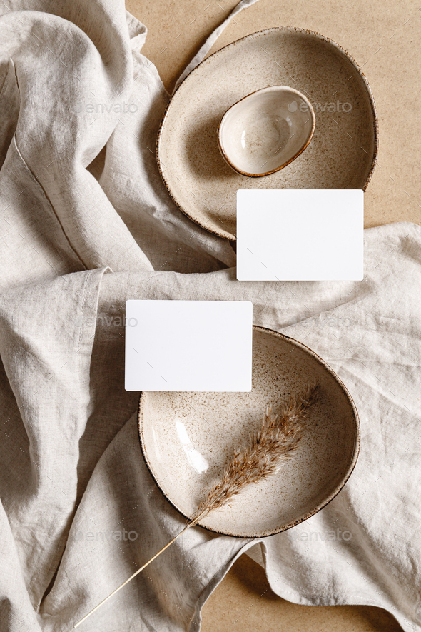 Blank paper sheet cards on bowls. Minimalist ceramics set over a linen cloth. - Stock Photo - Images