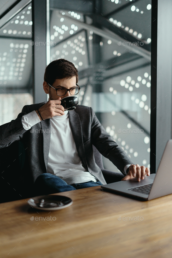 Successful business man working on laptop while drinking coffee - Stock Photo - Images