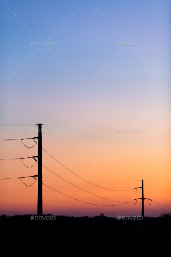 High voltage power tower over sunset clear sky, blackout concept - Stock Photo - Images