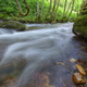Current in a river surrounded by large mossy rocks - PhotoDune Item for Sale