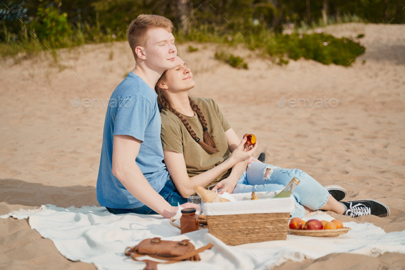Picnic on beach with food and drinks. Young boy and girl sunbathing - Stock Photo - Images
