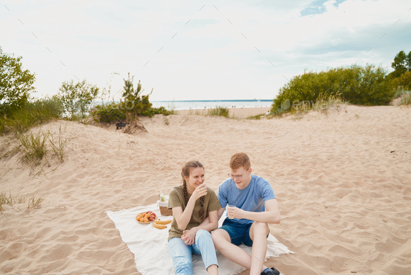 Picnic on beach with food and drinks. Young boy and girl sitting on sand - Stock Photo - Images