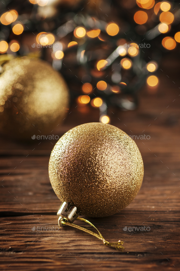 Christmas garland and gold balls on the wooden table - Stock Photo - Images