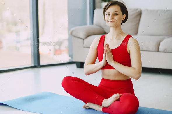 Girl in a red sports uniform make yoga at home - Stock Photo - Images