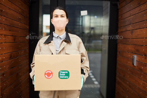 Courier holding box outdoors - Stock Photo - Images