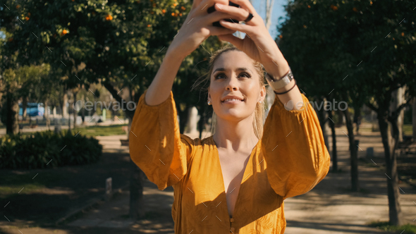 Young gorgeous woman taking photo on smartphone during walk along garden in city park - Stock Photo - Images