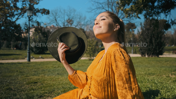Young beautiful woman in bright orange overalls with hat dreamily resting on lawn in park - Stock Photo - Images
