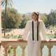 Gorgeous woman in stylish white suit standing on old balcony with amazing view on park - PhotoDune Item for Sale