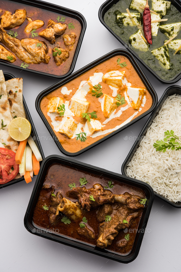 Online food delivery concept for Indian Restaurant showing plastic containers with food - Stock Photo - Images