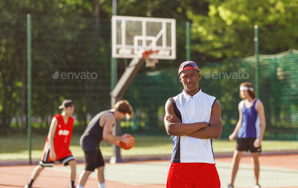 Serious African American basketball player and his multiracial team at outdoor court, blank space