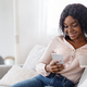 Home Leisure. Smiling african woman relaxing with smartphone and coffee on couch - PhotoDune Item for Sale