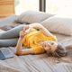 Cheerful young girl with laptop and mobile phone browsing net on bed at home - PhotoDune Item for Sale