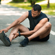 Sports injury. African American runner sitting on jogging track and feeling pain in his ankle - PhotoDune Item for Sale