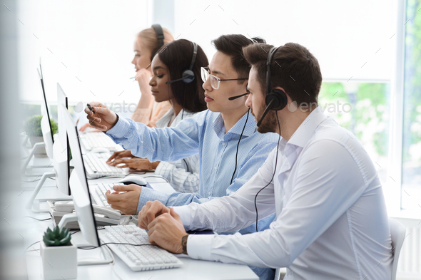 Customer support service. Hotline operator helping his colleague at call centre office - Stock Photo - Images