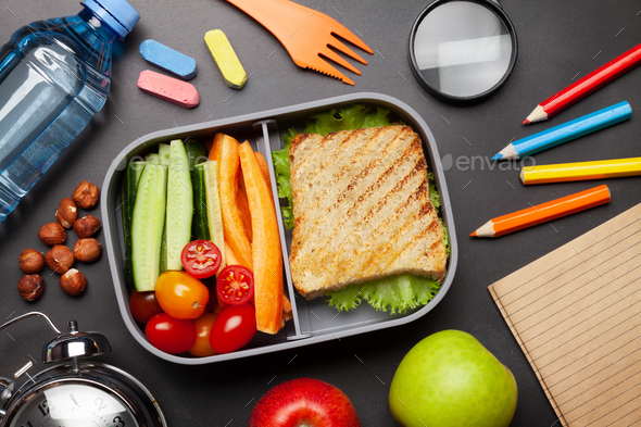 School lunch box and education stationery on stone table - Stock Photo - Images