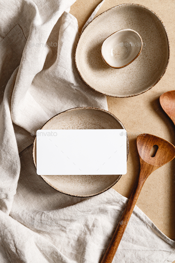 Blank paper sheet card on a bowl.  Minimalist ceramics set over a linen cloth. - Stock Photo - Images