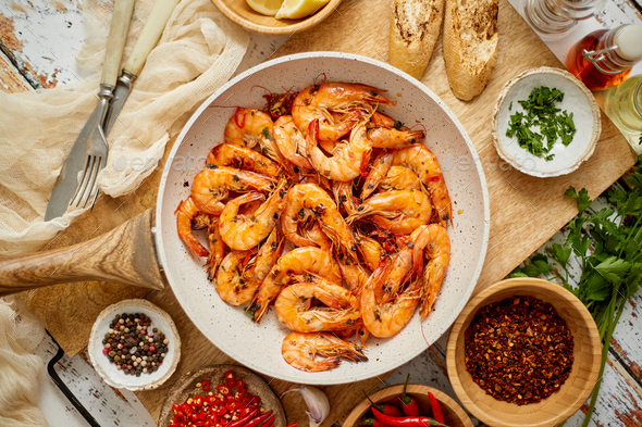 Roasted Prawns on frying pan served on white wooden cutting board - Stock Photo - Images