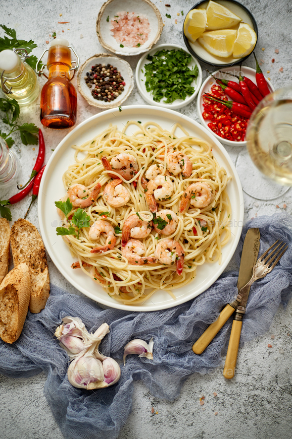 Spaghetti with shrimps on white ceramic plate and served with glass of white wine - Stock Photo - Images