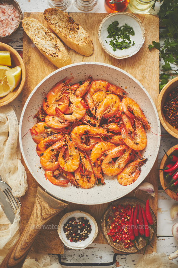 Traditional fried tiger prawn with garlic bread as top view served in a white frying pan - Stock Photo - Images